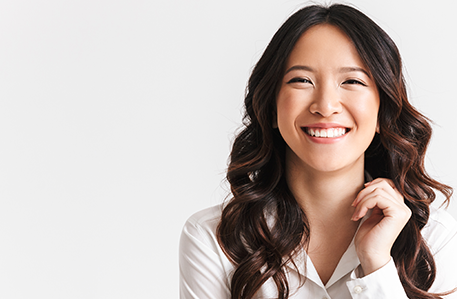 Portrait of gorgeous asian woman with long dark hair laughing at camera with beautiful smile, isolated over white background in studio